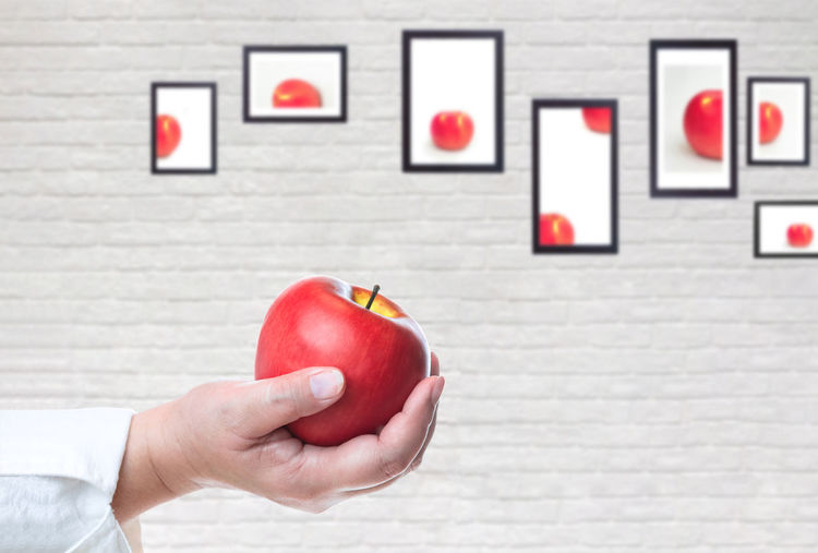 Cropped image of man holding apple against wall