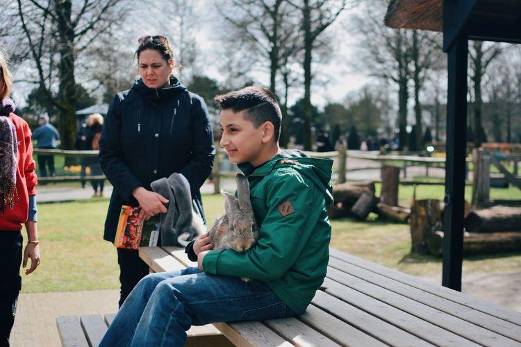 Men sitting on bench holding rabbit