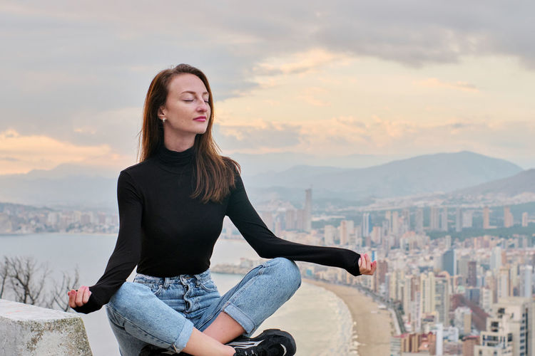 Young woman sitting on city against sky during sunset