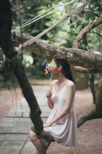 Woman holding colorful pinwheel toy while sitting on branch at park