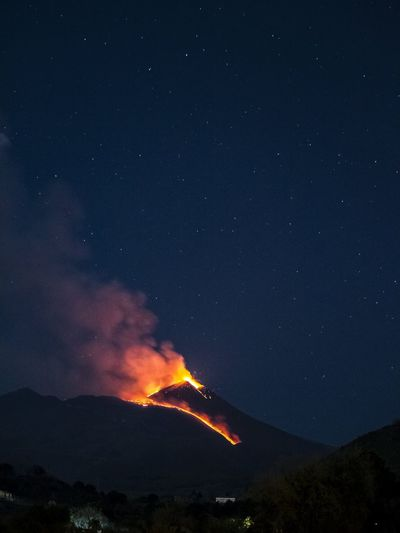 Panoramic view of the etna volcano illuminated by lava and the night sky.