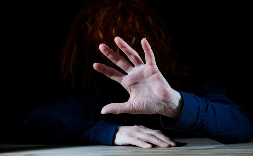 a woman is sitting in the dark and raises a hand defensively Human Hand Hand Human Body Part Indoors  One Person Studio Shot Body Part Black Background Real People Finger Unrecognizable Person Adult Attack Defense Self-defense Dangerous Danger Woman Violence Symbol Aggression  Emotion Strength
