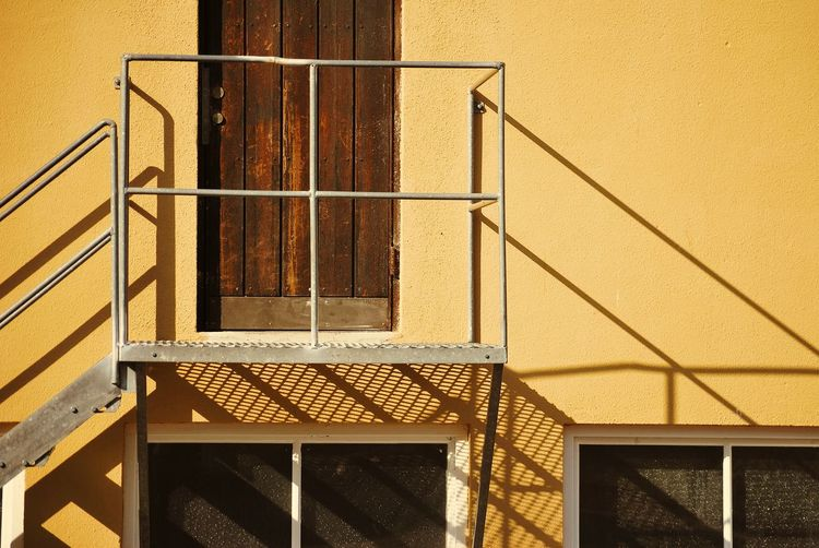 Shadow of railing on wall of building