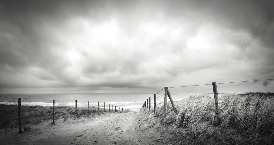 Pathway Leading Towards Sea Against Cloudy Sky
