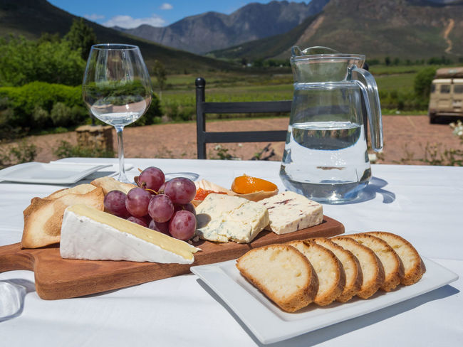 Cheese platter served at vineyard in winelands near Cape Town, South Africa South Africa Winelands Bread Breakfast Cheese Close-up Day Drink Drinking Glass Food Food And Drink Franschhoek Freshness Grape Healthy Eating Mountain No People Outdoors Plate Ready-to-eat Sausage Table White Wine Wine Wineglass