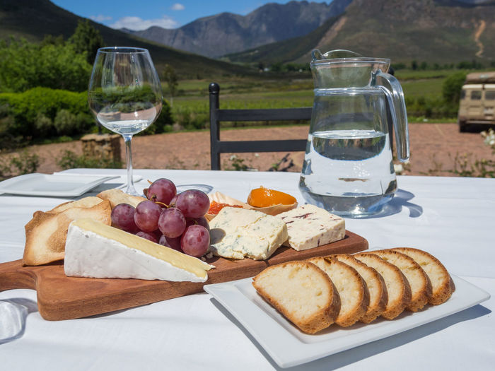 Close-Up Of Cheese Plate And Bread At Wine Tasting On Vineyard In South Africa