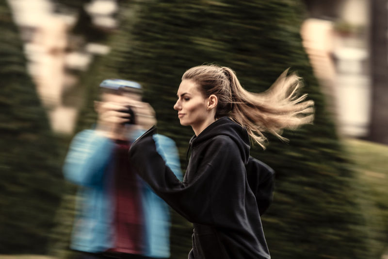 Adult Blurred Motion Camera - Photographic Equipment Day Focus On Foreground Leisure Activity Lifestyles Motion Nature One Person Outdoors Paparazzi People Photographing Photography Themes Real People Side View Technology Tree Waist Up Wireless Technology Women Young Adult Young Women