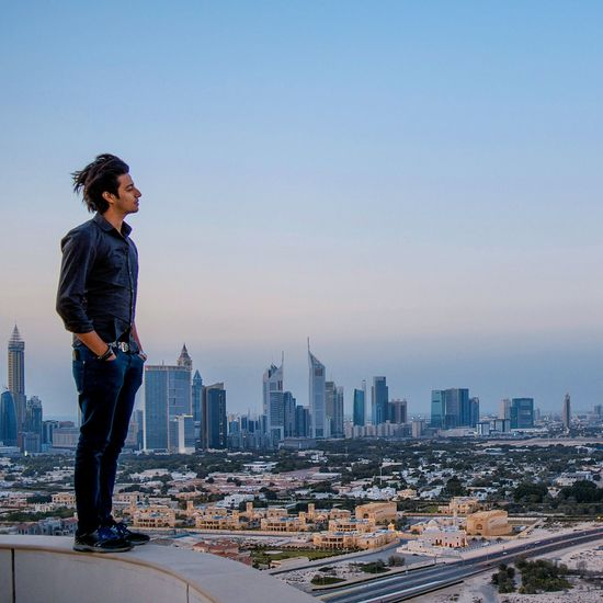Full length of young man standing on building terrace looking over cityscape
