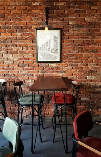 Empty chairs and tables in front of wall