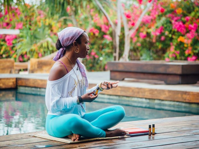 Wellness Meditation Chakras Healing Yoga Pose Yoga Sitting Water Women Full Length Nature One Person Real People Lifestyles Swimming Pool Outdoors Clothing Females Leisure Activity