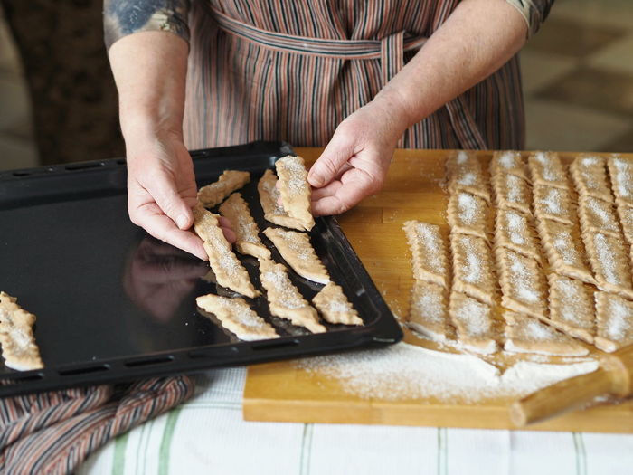 An elderly woman is hands place sliced raw biscuits on a baking sheet in the oven.