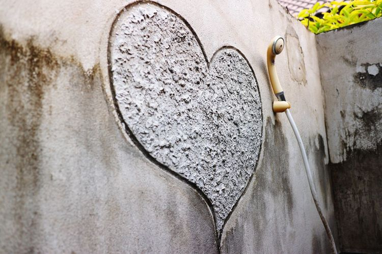 Low angle view of heart shape on wall by shower handle in bathroom