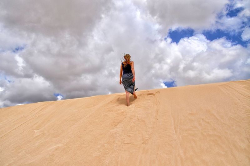 Rear View Of Woman Walking On Sand Dune Against Cloudy Sky