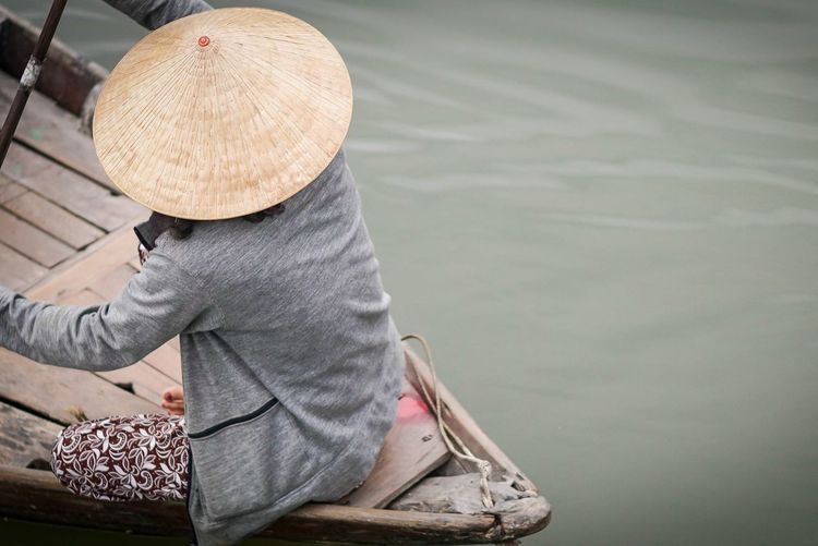 High angle view of woman wearing hat sitting in nautical vessel on lake