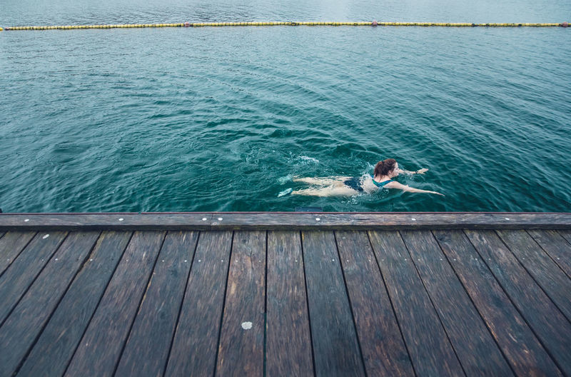 High angle view of man swimming on pier over sea