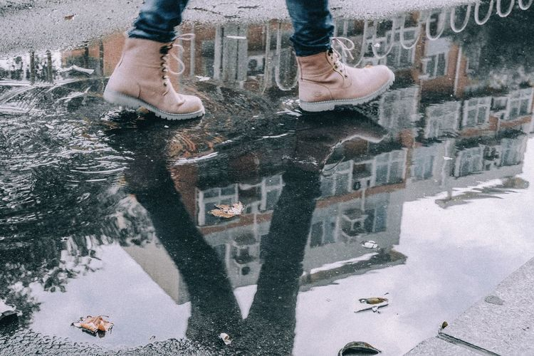 Low section of person with reflection in puddle
