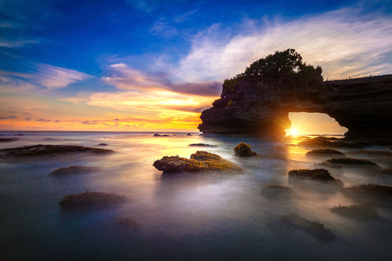 Scenic view of pura tanah lot in sea against sky during sunset