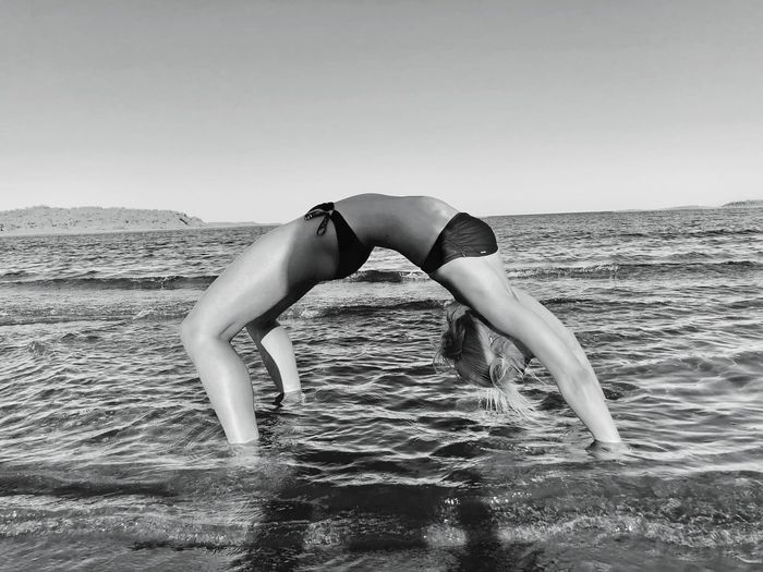Side view of young woman wearing bikini while exercising in sea on shore at beach