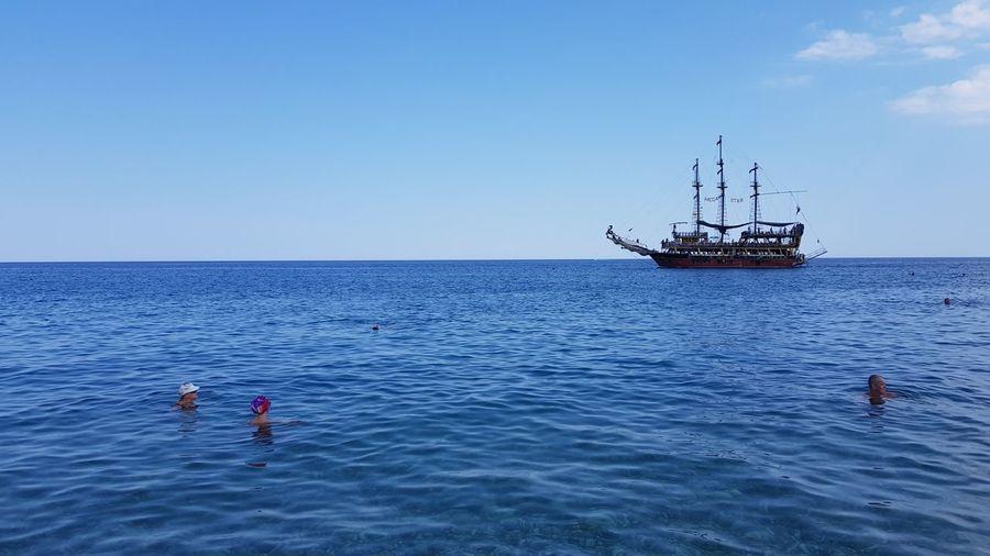 Men in sea against clear sky