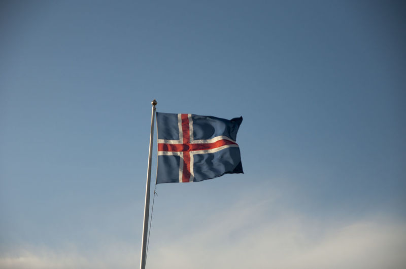 Icelandic Flag Blows in the Breeze Blue Clear Sky Copy Space Flag Hanging High Section Iceland Identity Low Angle View Multi Colored National Flag No People Outdoors Patriotism Pole Red Single Object Sky Sunlight Wind Windy