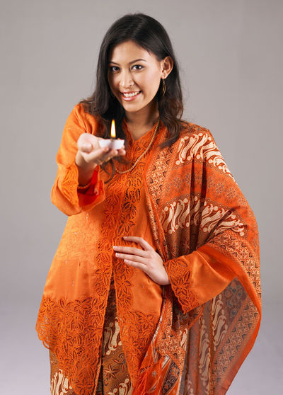 Portrait Of Smiling Woman Holding Diya Against Gray Background