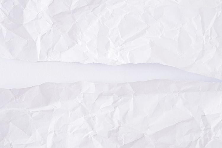 Full frame shot of torn paper against white background