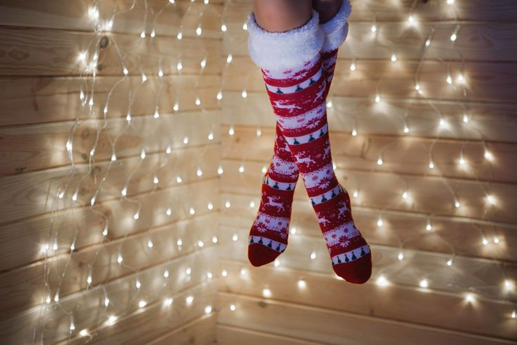 Low section of woman wearing socks in illuminated home during christmas
