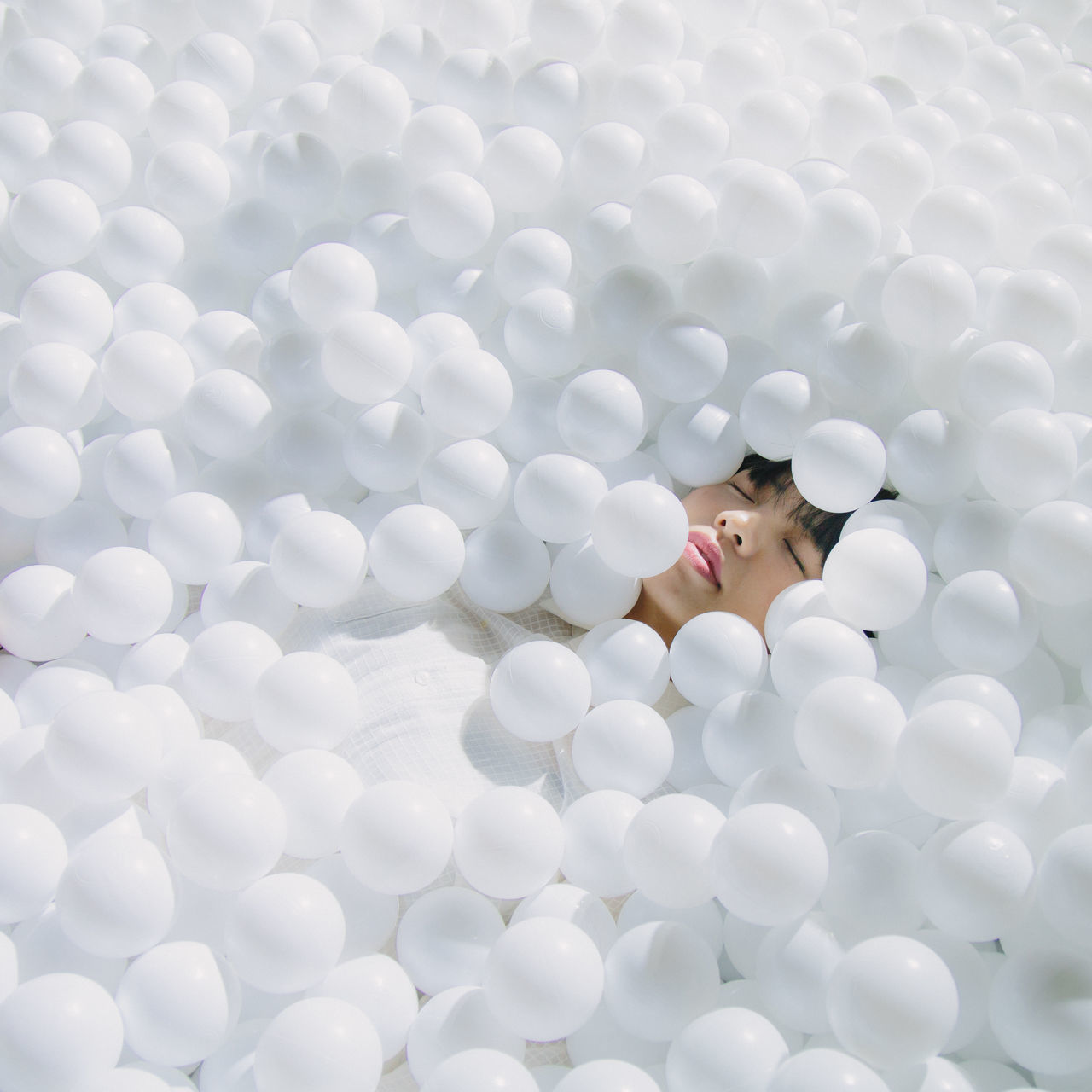 High angle view of woman sleeping amidst balls
