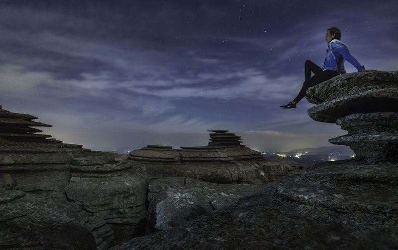 Low angle view of man on rock against sky at dusk