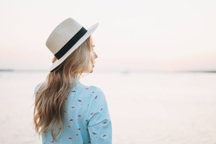 Beautiful blonde young woman in blue dress and straw hat on pier on sunset