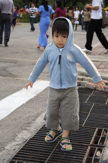Portrait of cute boy wearing hooded shirt while standing on sewage