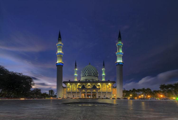 Illuminated mosque against sky at night