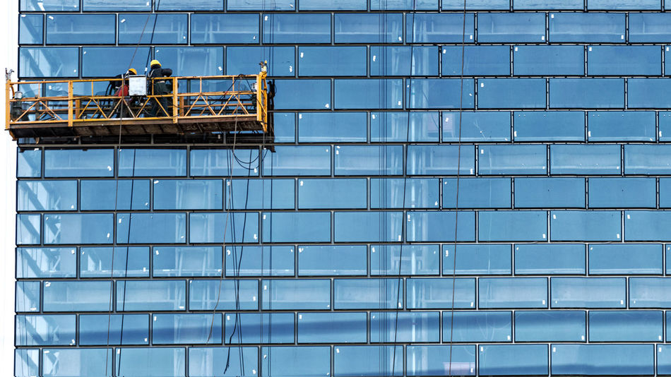 Workers, standing in the ropes installation basket, wash skyscraper windows from the outside. Architecture Building Exterior Built Structure Construction Site Construction Worker Day Development Manual Worker Men Occupation Outdoors People Standing Teamwork Two People Window Washer Working Fresh On Market 2017