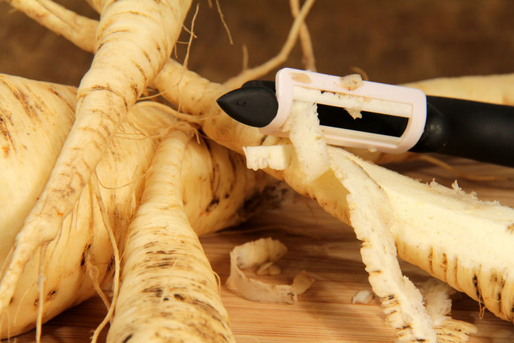 Close-Up Of Peeler Peeling Vegetable On Table