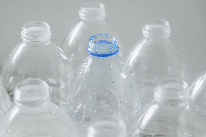 Close-up of glass bottle against water