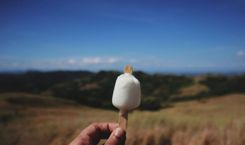 Person holding ice cream against sky