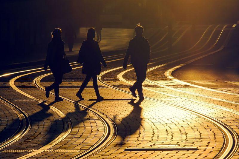 People walking at railway track on road