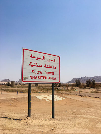 Slow Down Inhabited Area Road Sign in Saudi Arabia Arabic Saudi Arabia Middleeast Signage Slow Down Road Outdoors Land Guidance Blue Climate Environment Scenics - Nature Non-urban Scene Arid Climate Copy Space No People Western Script Nature Desert Landscape Sky Sign Highway