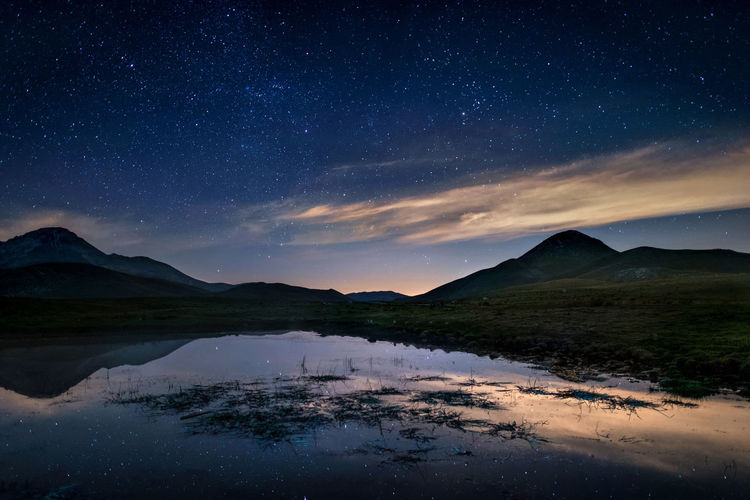 Scenic view of lake and mountains against sky at night