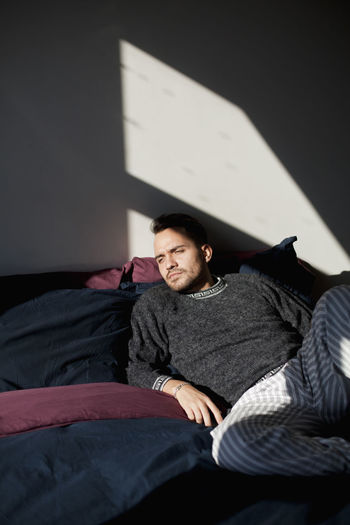 Portrait of young man resting on bed at home