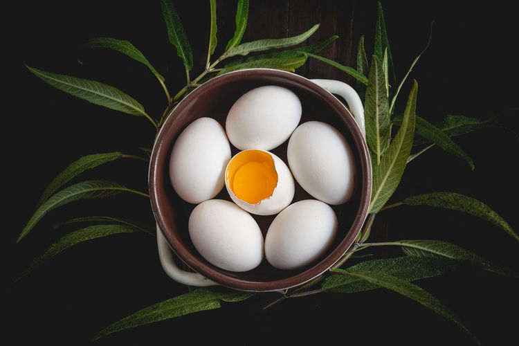 High Angle View Of Eggs In Bowl With Leaves On Black Background