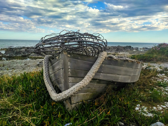 Lost Boat. Woodenboats Kaikoura Nature Boat Clouds And Sky Rope Wooden Wood Old Oldboat Shipwreck Boat WoodenBoat Rope Clouds And Sky Sea Horizon Over Water Beach Water Sky Cloud - Sky Tranquility Day No People Nature Outdoors Grass Beauty In Nature