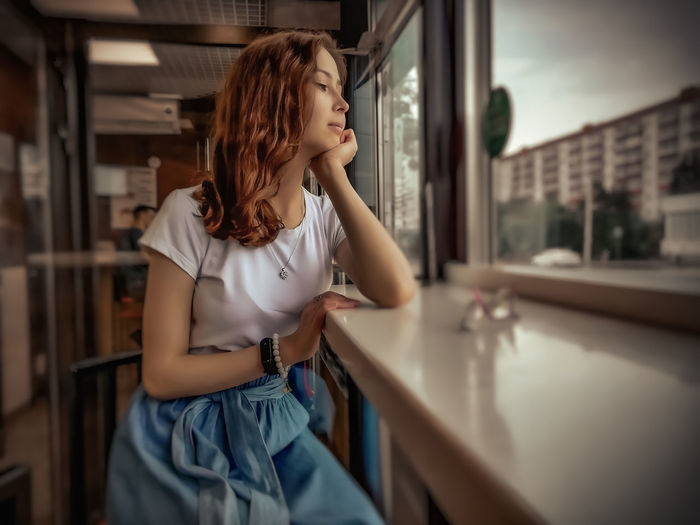 Young woman looking away while standing at home