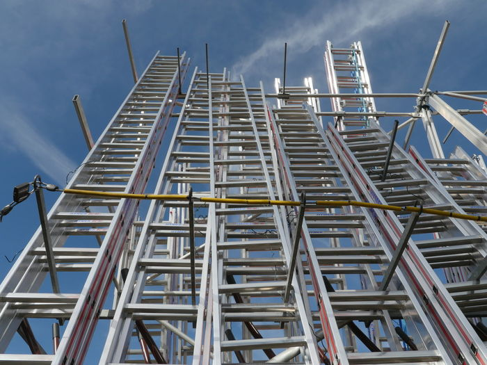 Low angle view of metallic ladders against sky