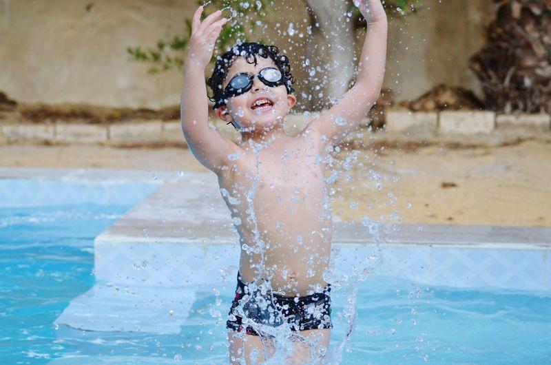 Shirtless boy playing in swimming pool