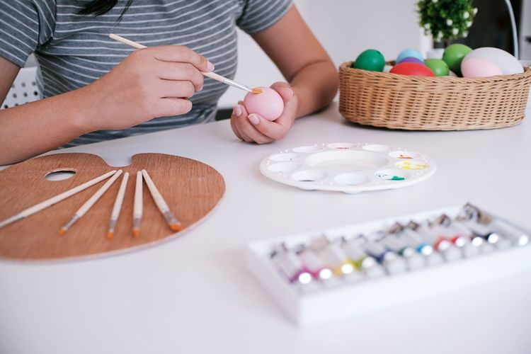 Midsection of woman painting easter egg while sitting at table