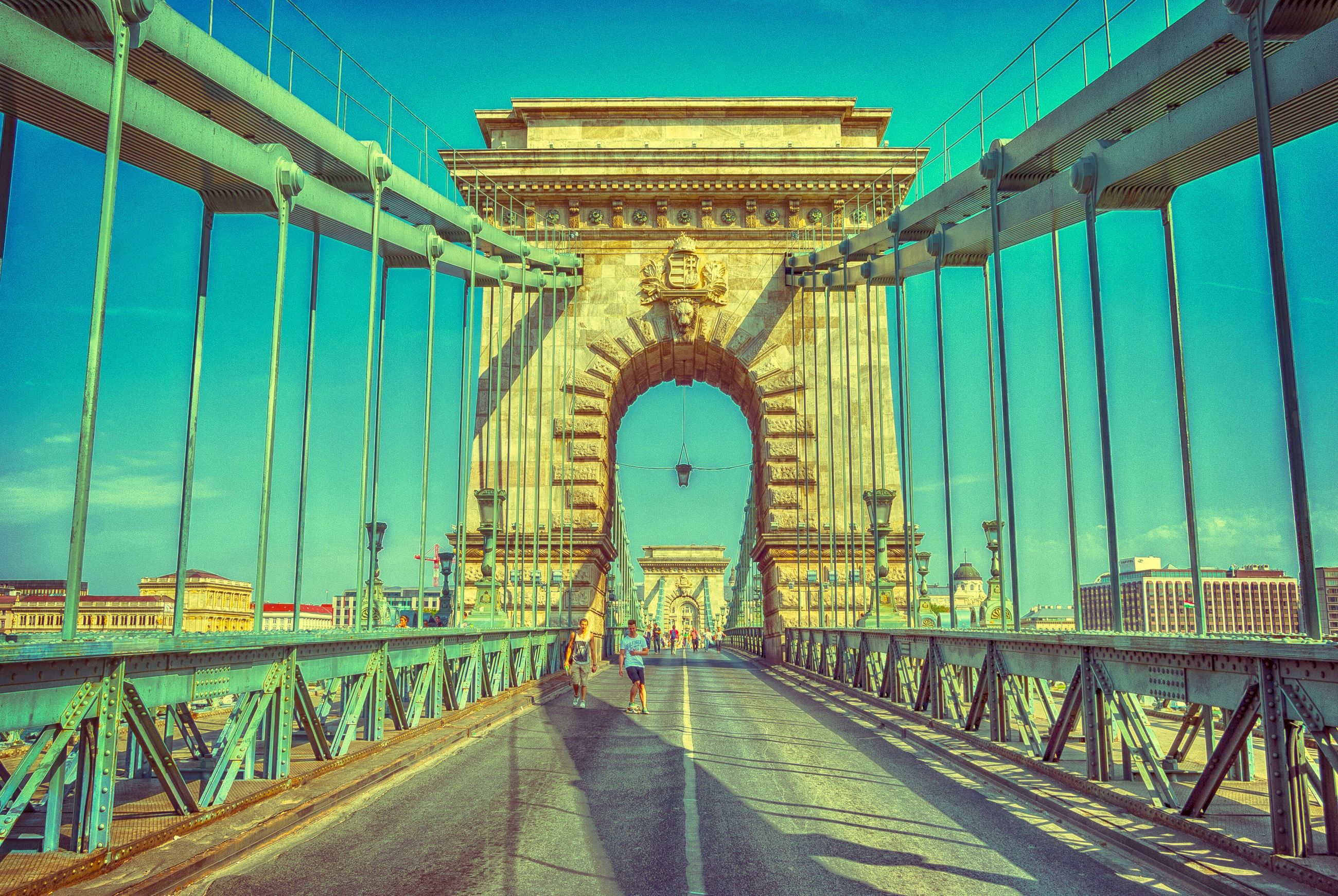 architecture, built structure, tourism, travel destinations, famous place, suspension bridge, connection, blue, travel, bridge - man made structure, engineering, international landmark, vacations, arch, the way forward, water, history, sky, outdoors, day, sea, the past, city life, architectural column, national landmark, architectural feature, scenics