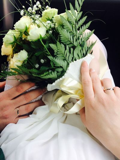 Cropped hands of bride and groom holding bouquet