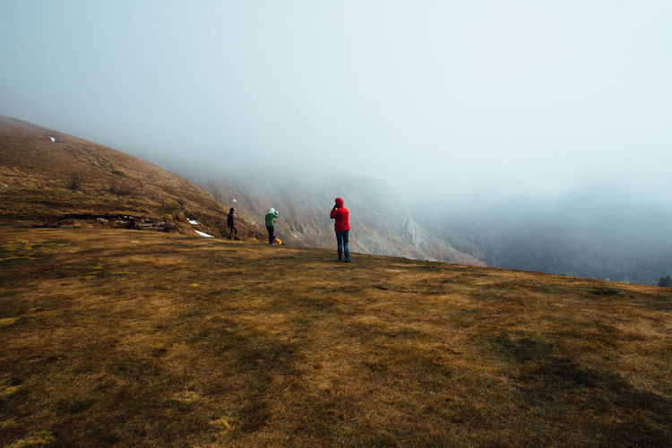 Friends standing on mountain during foggy weather