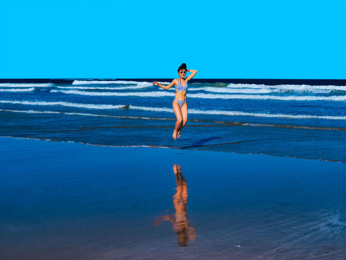 Happy young woman with a beautiful body living a healthy lifestyle jumping waves on beach shore